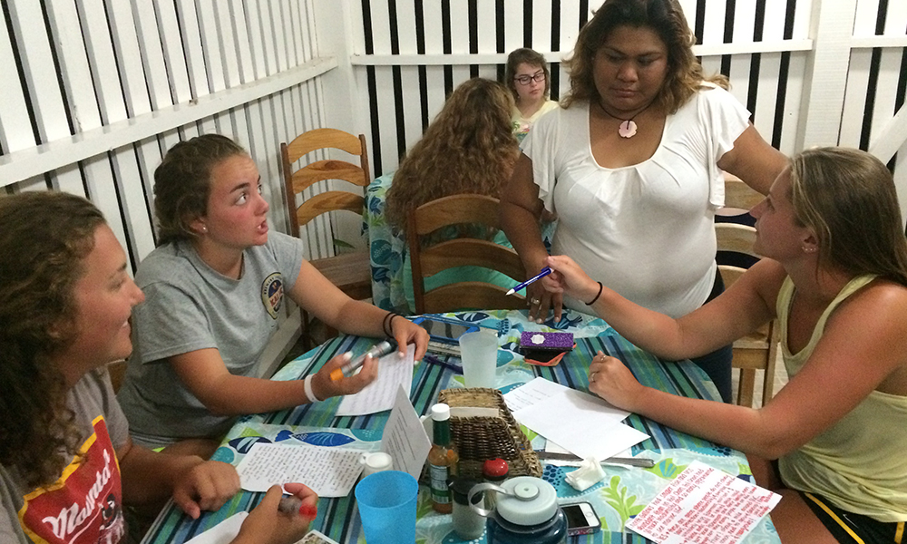Ecomar staff assisting the Service Scholars with their small group discussion on how best to protect Belize's marine wildlife and resources. (Photo Credit - Finn Belanger)
